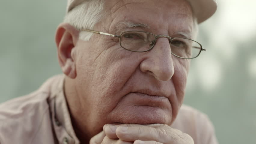 Seniors portrait, sad elderly man with white hat and glasses looking at camera