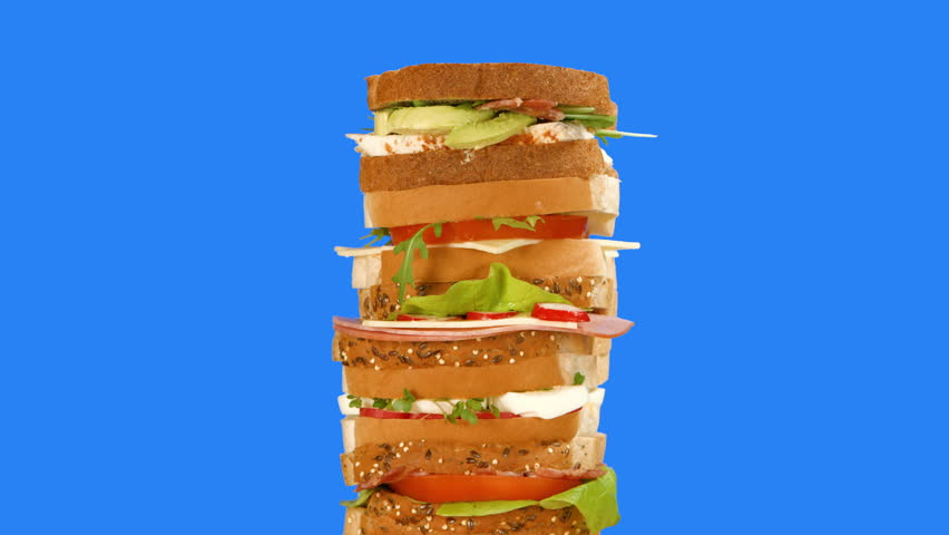 Sandwiches animate upwards to form a tall stack made from a variety of breads and fillings, such as eggs, tomato, cheese, avocado. The stack is filmed against a blue backdrop for easy keying.