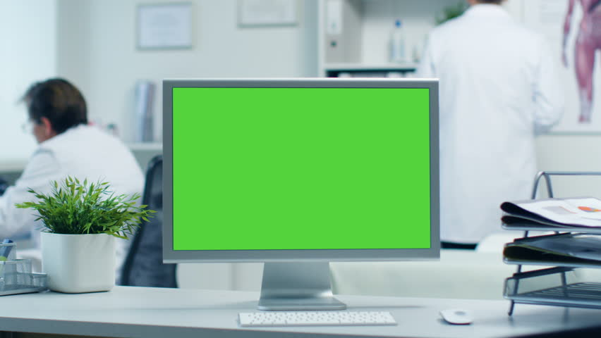 Close-up of a Monitor with Green Screen. Doctor Works with Folders, Assistant Talks with Patients on the Phone. Office is Modern and Light. Shot on RED Cinema Camera 4K (UHD). | Shutterstock HD Video #23570845