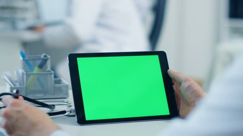 Close-up of a Male Doctor Uses Tablet Computer with Green Screen, He also Holds Pen and Makes Notes, His Assistant Works in the Background. Office is  Modern. Shot on RED Cinema Camera 4K (UHD).