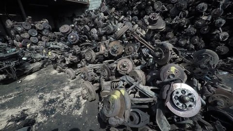 Messy. disorganized. unstable pile of steel car axles and wheel parts at a junkyard and recycling center.