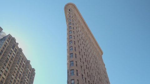 LOW ANGLE VIEW, CLOSE UP: Famous Flatiron iron shaped building with limestone and glazed terracotta facade in New York City, parallel to Fifth Avenue and Broadway streets on beautiful sunny summer day