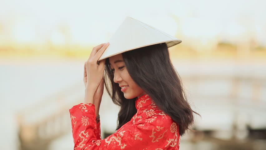 Vietnam girl in the national red dress Ao Dai posing and smiling for the camera on the seafront of Da Nang.