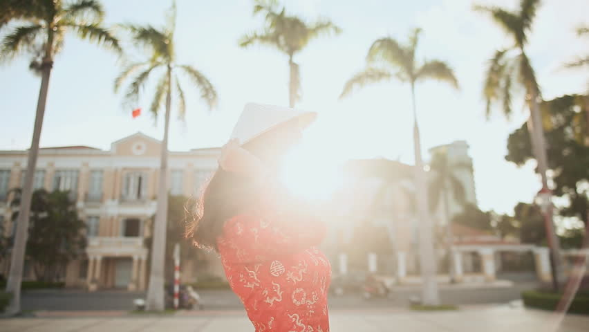 Vietnamese girl puts on a national cap Non La in the rays of the evening sunset in Da Nang