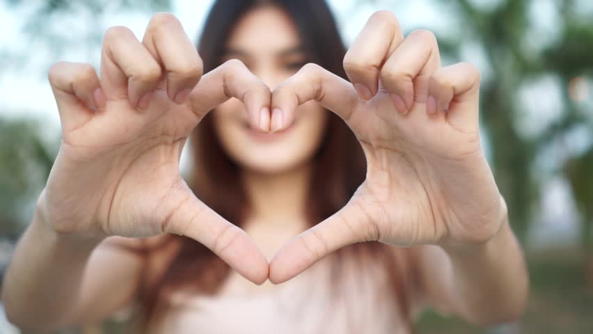 Slow motion : Young woman making heart shape by her hand and smiling   Shutterstock HD Video #23641420