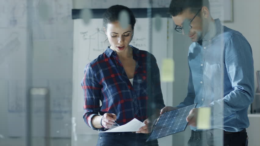Late at Night Male and Female Solar Engineers Discuss Drafts and Part of a Solar Panel. Woman Holds Drafts, Man Hold Panel. In the Background Whiteboard with Sketches, Pinned to the Wall Blueprints.    Shutterstock HD Video #23651740