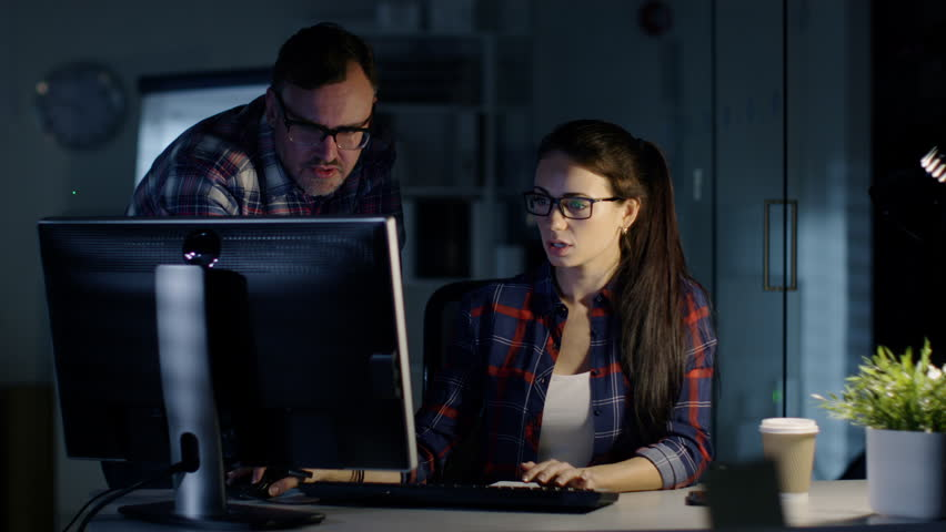 Late Night at the Office. Male and Female Colleagues Discuss Work Done on Her Personal Computer. In the Background Man Working at His Desk. Shot on RED Cinema Camera 4K (UHD). | Shutterstock HD Video #23652850