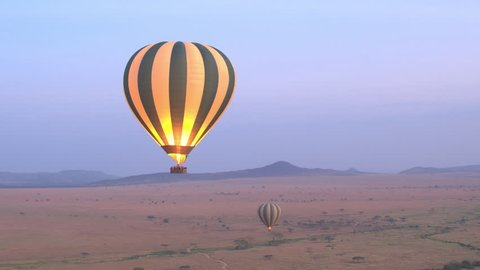 AERIAL: Safari hot air balloon flying above vast savanna plain rolling into the distance in Serengeti National Park at purple light dawn. Tourists traveling in air over African wilderness at sunrise