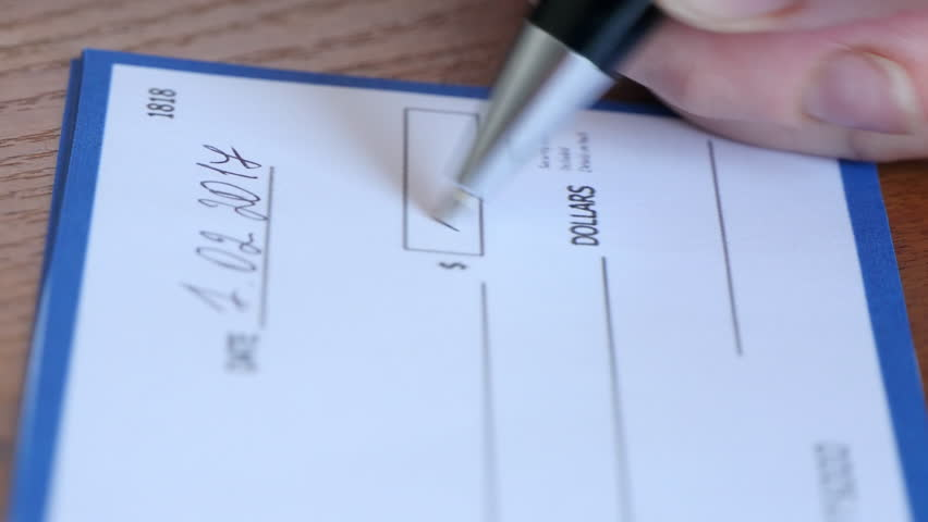 Close-up of human hand filling check.