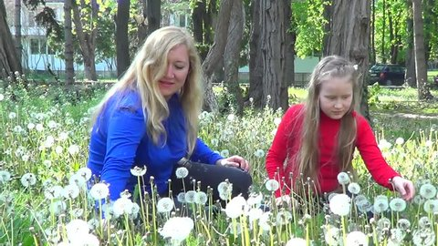 Mother and daughter on meadow with white dandelions