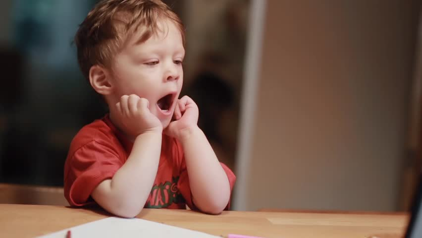 Yawing baby boy in red shirt sitting at the table and watching on tablet holds his hands near face