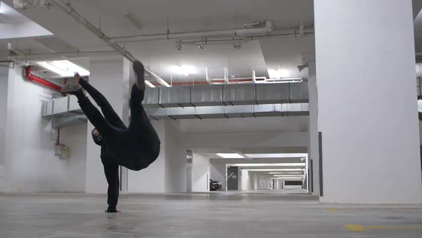 Young Man Breakdancing in Car Park with Hoodie in Slow Motion Dolly Shot | Shutterstock HD Video #23723980
