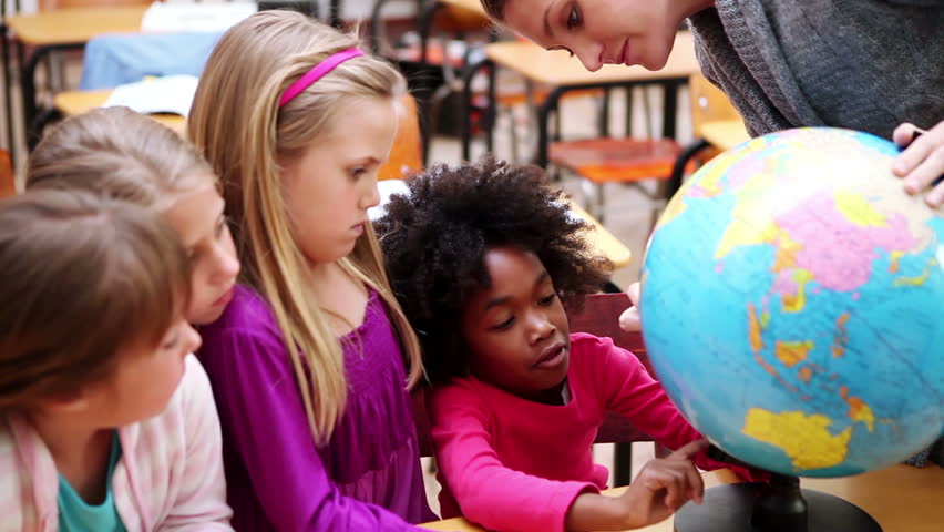 Happy pupils looking at a globe in the classroom