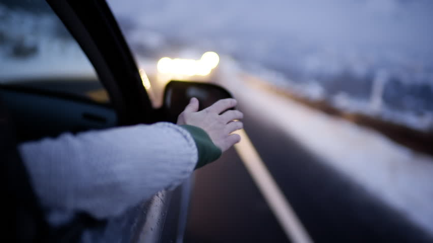 Young Woman Holds Her Arm Out Of Car And Feels The Breeze On A Cold Winter Night (Slow Motion Closeup)
