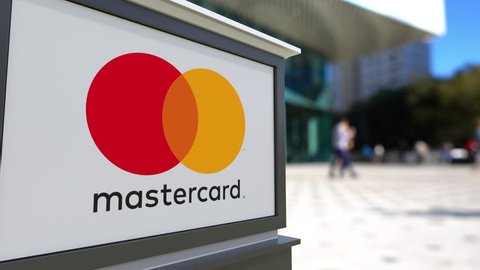 Street signage board with MasterCard logo. Blurred office center and walking people background. Editorial 3D rendering 4K