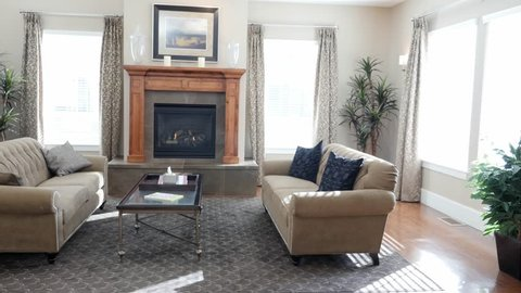 A dolly shot of a modern and beautiful room with a fireplace and couches