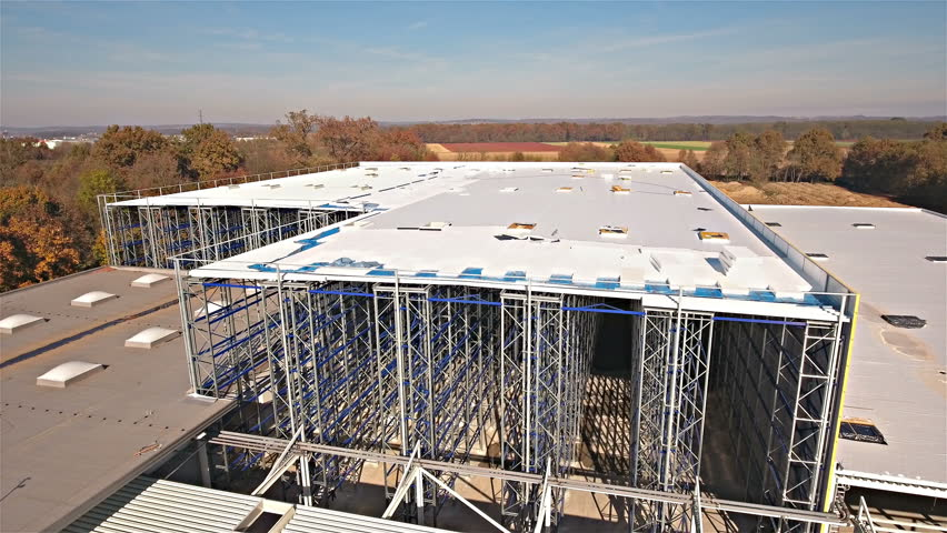 Flying closer to warehouse frames while being built 4K. Aerial bird's eye view of big warehouse in focus on a sunny day. Descending drone.