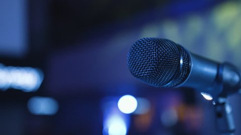 Microphone on the Stand is Standing on the Stage, Close-Up Microphone on the Background of the Auditorium, Spotlight, Backlight People Gather in the Hall and Sit on Seats, Waiting For Performances 4k