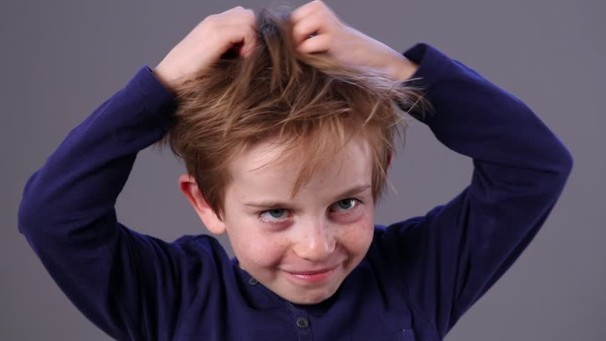 closeup of a cute small child with freckles and red hair scratching his head for skin itching, grey background, indoors