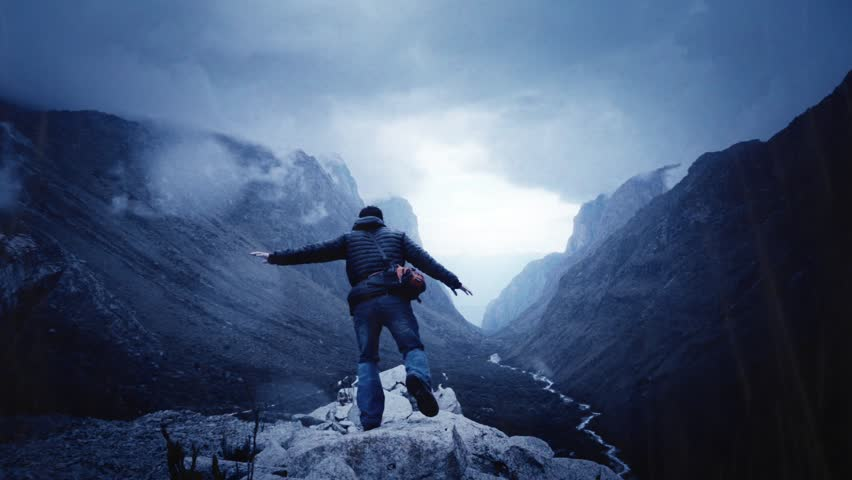 Man jumps on the rocks of a panoramic view on Huascaran Natural Park to escape of the storm. Slow motion #23863330