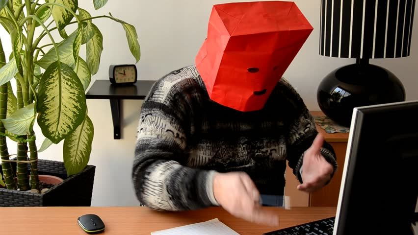 Introverted fat man in red paper bag animatedly speaks with on-line psychologist looking at monitor on the desk. Man needs a psychotherapist but he still hesitates to open his face