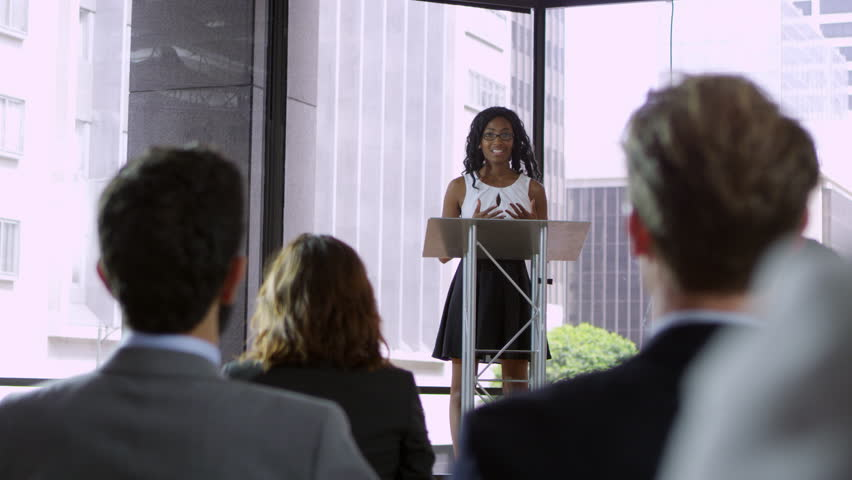 Young black woman presenting seminar to a business audience, shot on R3D