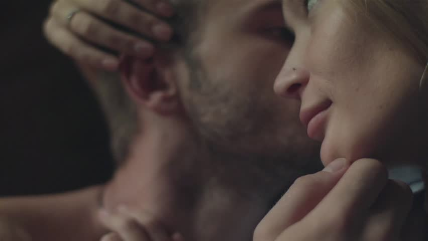Couple having sweet moments stroking each other intimate scene head close up.  Lovers cuddle kissing. Young woman run fingers through boyfriends hair caressing his ear and man touch girlfriends nose
