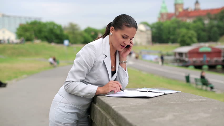 Businesswoman with documents and cellphone in the city    Shutterstock HD Video #2393690