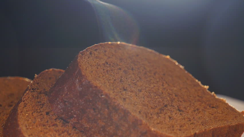 Hot and fresh brown bread. Steam comes out. Handmade black bread on black background. Slow motion.