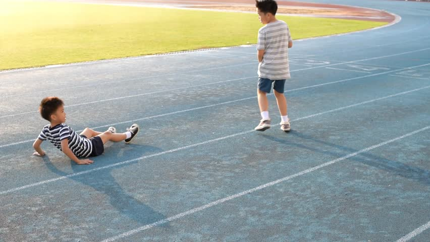 Young Asian boy running on blue track, fall and help by another boy.