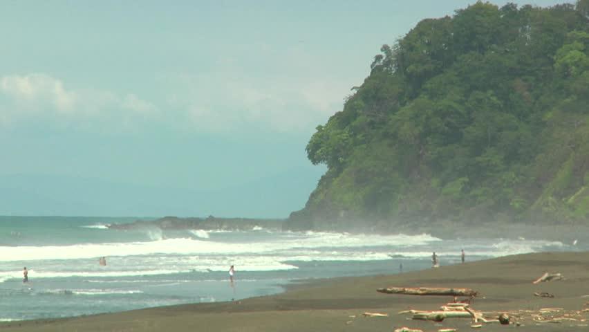 Beach and ocean near a rocky cliff with natural surroundings(wide shot). Toma amplia de la playa con peñazco con vegetación natural al fondo.