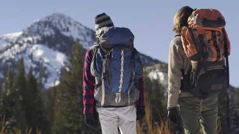 Backpackers Take A Moment To Look At Snow Covered Mountain Before Continuing On Their Way