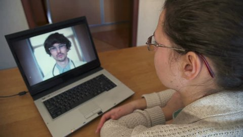 Woman In Kitchen Using Laptop - Online Chat with Doctor on Screen