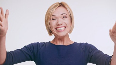 Blonde beautiful middle-aged woman loudly saying wow showing ok and smiling at camera standing on white background in blue sweatshirt