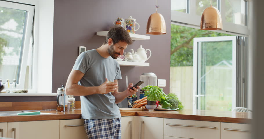 Attractive man at home using smartphone in kitchen drinking coffee sending message on social media smiling enjoying modern lifestyle