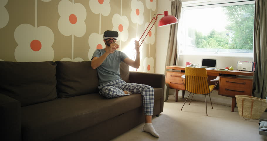 Young Man wearing virtual reality headset sitting on sofa at home watching 360 video imagination concept | Shutterstock HD Video #24027940