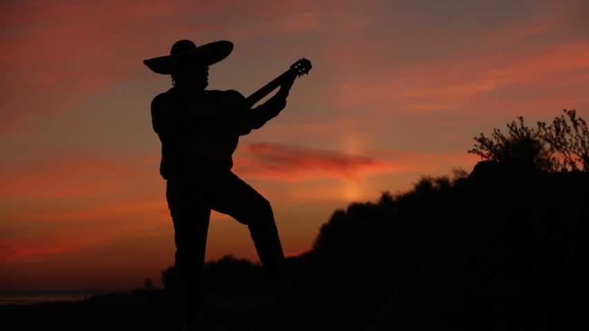 Spanish musician playing guitar on sunset background. Silhouette video