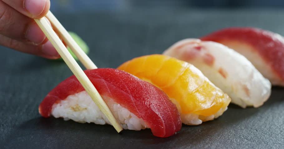 Macro shot of sushi, sashimi, uramaki and nighiri. typical Japanese dish consisting of rice, salmon or tuna,shrimp and fish eggs soaked in soy. Concept: Japanese restaurant, sushi, oriental tradition.