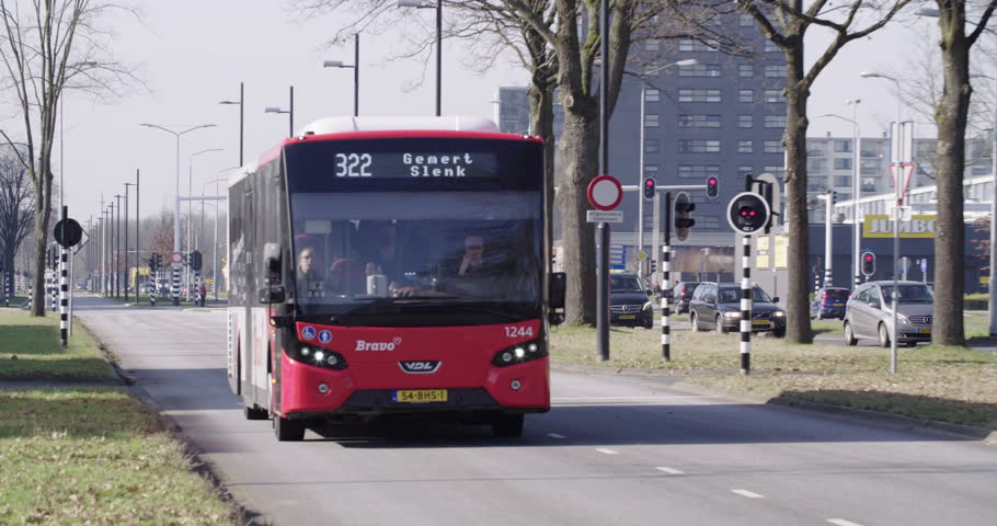 EINDHOVEN, NETHERLANDS - FEBRUARY 15, 2017: Red city bus transporting passengers on ring road