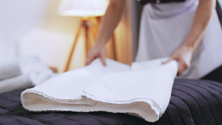 Middle-aged Caucasian female chambermaid folding towels on bed in slowmotion