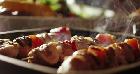 cinemagraph of skewers of meat with vegetables cooked on a spit in a pan
