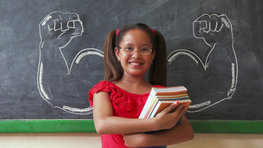 Concept on blackboard at school. Young people, student and pupil in classroom. Intelligent and successful hispanic girl in class. Portrait of female child smiling, looking at camera, holding books