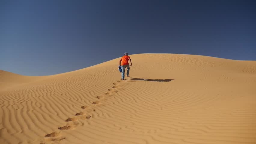 SAHARA DESERT, TUNISIA - CIRCA OCTOBER 2015:  a man walks barefoot on the fine sand of a dune in the Sahara desert in a sunny day. | Shutterstock HD Video #24137140