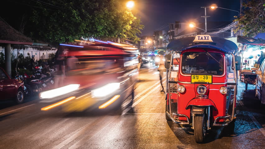 Chiang Mai, Thailand - February 19, 2017: Timelapse view of night traffic with tuk-tuk parked on the side of the street, Chiang Mai, Thailand.