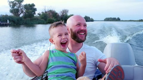 Father and son spend time together, emotionally respond during fast driving on speed boat, family on summer vacation, good dad at weekend with child