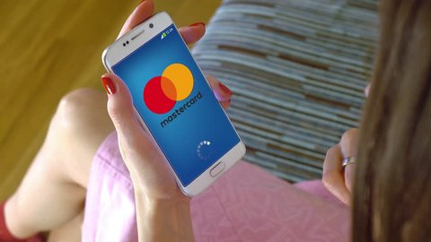 Young woman holding a cell phone with loading Mastercard mobile app. Conceptual editorial 4K clip