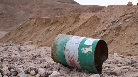 Old green rusty cask in desert. Iron barrel lies on the stony ground in Aqaba, Jordan