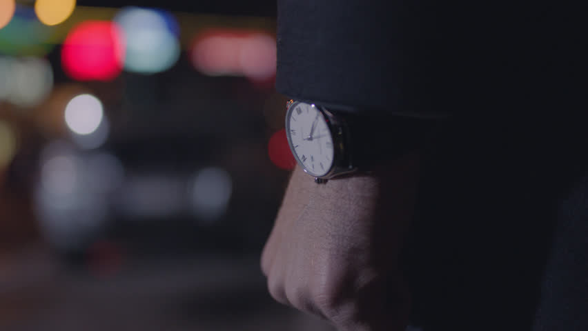Close Up of an Expensive Wristwatch on an elegantly dressed Man walking the streets of city at night. | Shutterstock HD Video #24208471