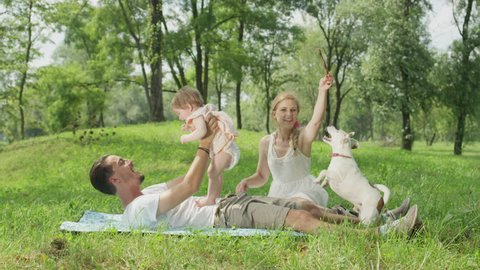 SLOW MOTION, CLOSE UP, DOF: Smiling young dad lying on blanket, playing having fun with cheerful sweet baby daughter. Beautiful mum sits beside and plays with cute little pet dog chasing a stick