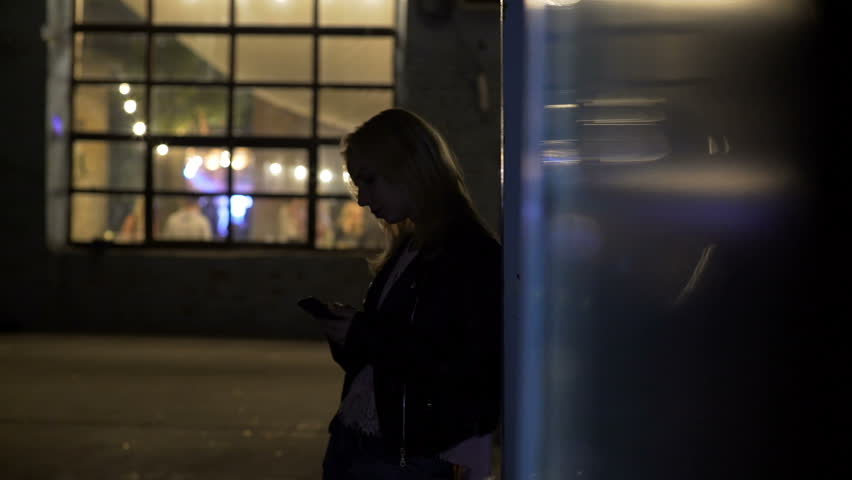 Lonely girl standing on alley near nightclub and calling taxi, night life #24233120